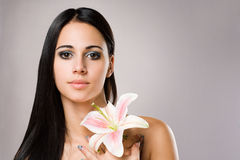 Serene brunette beauty with colorful flower. Stock Photography