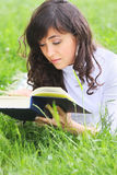 Serene brunette reading book on grass Stock Images