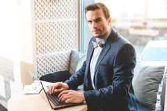 Serene businessman using notebook computer. I like my job. Portrait of serious stubbled male working on laptop while situating in cozy office. He looking at Stock Image