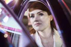 Serene businesswoman opening car door at night, close-up, reflected lights Royalty Free Stock Photos