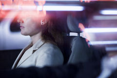 Serene businesswoman sitting in the car at night, illuminated and reflected lights on the car window Royalty Free Stock Photography