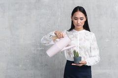 Serene businesswoman watering a flowerpot royalty free stock photos