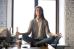 Serene calm business woman sit on office desk meditating royalty free stock image