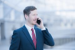 Serene and calm man talking on the phone. Portrait of a handsome man talking on the phone. He`s wearing a dark blue business suit and red neck tie Stock Photo