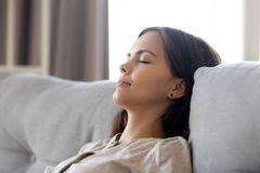 Serene calm woman relaxing leaning on comfortable couch having nap royalty free stock photo