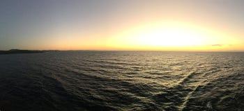 Serene Caribbean Sea Sunrise. Dynamic orange and yellow blasting upon clouds Royalty Free Stock Photos