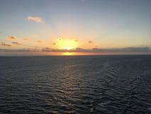 Serene Caribbean Sea Sunrise. Dynamic orange and yellow blasting upon clouds Stock Image