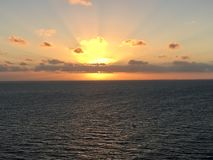 Serene Caribbean Sea Sunrise. Dynamic orange and yellow blasting upon clouds Stock Photo
