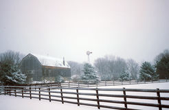 Serene Country Farm Scene in Snow. Old barn and split rail fence nestled among fir trees dusted with snow in this peaceful country scene Stock Photo