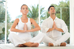 Serene Couple Doing Yoga. Young Couple Sitting In A Lotus Pose And Meditating While Exercising At Yoga royalty free stock photography