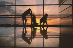 Serene couple waiting for flight. Full length side view bored male situating opposite orderly lady. She typing in mobile while sitting on luggage trolley in Royalty Free Stock Photography