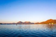 Serene dawn shot of lake with mountains in the distance. Serene dawn shot of fateh sagar lake udiapur india. The beautiful blue water with waves and the golden Stock Image