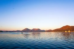 Serene dawn shot of lake with mountains in the distance. Serene dawn shot of fateh sagar lake udiapur india. The beautiful blue water with waves and the golden Stock Photo