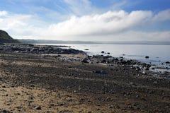 Serene day over the black rocks Stock Images