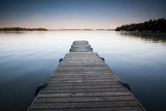 Serene Dock. This dock floats on water like glass inviting you to jump on in Stock Images
