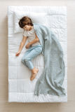 Serene dreamy kid covered with blue blanket Royalty Free Stock Image