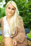 Serene Enigmatic Blonde Beauty. Serene beauty, an enigmatic sexy young blonde model sits on a park bench in a tan jersey Royalty Free Stock Photo