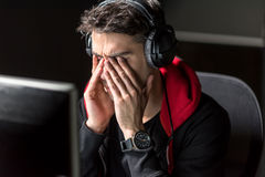 Serene exhausted male rubbing face at desk. Serious man wiping eyes after long work in front of screen of digital device. He hearing song while sitting at table Stock Image