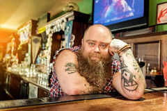 Serene fat bartender reclining on worksurface. It is long hours during job. Portrait of calm bearded man showing boredom while leaning on counter in pub Stock Images