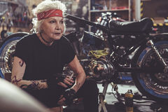 Serene female retire fuming near motorcycle Royalty Free Stock Images