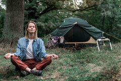 Serene girl enjoying meditation in the woods. Enjoying peace in nature. Full length portrait of calm young woman meditating in forest. She is sitting in lotus Royalty Free Stock Photos