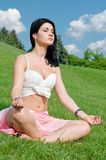 Serene girl meditating on grass. Beautiful girl meditating cross legged on grass with a serene expression and her eyes closed Stock Photography