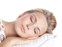 Serene girl sleeping. Closeup portrait of cute blond serene girl sleeping, attractive gentle female with closed eyes lying down on the pillow isolated on white Royalty Free Stock Image