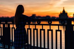 Serene girl standing alone on waterfront in front of fence of embankment. royalty free stock images