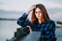 Serene girl standing alone on waterfront in front of fence of embankment royalty free stock photography