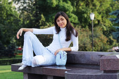 Serene girl on stone bench Royalty Free Stock Photos