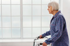 Serene grandmother going with walking frame in hospital Royalty Free Stock Photo