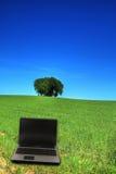 Serene grassland and a notebook. Nature versus modern technology Stock Image