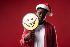Serene guy with closed eyes holding yellow emoji. Need some sleep. Handsome man in santa hat posing with carton icon of smiling face. on red background stock photos