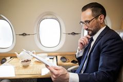 Calm passenger enjoying his first class flight. Serene handsome man reading newspaper while sitting in comfortable airplane seat at tray table Stock Images