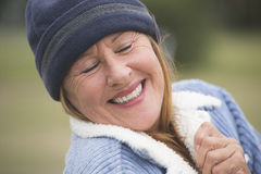 Serene happy woman warm bonnet and jacket Stock Photos