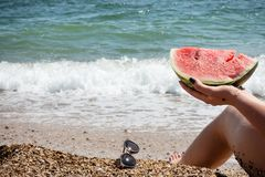 Serene holiday on the seashore with a ripe watermelon stock image
