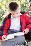 Serene kid reading book in park. Serene kid in red jacket reading book in autumn park Royalty Free Stock Photo