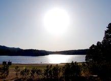 Serene Lake con il Sun direttamente al di sopra Fotografia Stock