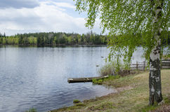 Serene lake view. With an old wooden rowing boat at springtime at springtime Royalty Free Stock Photography