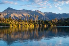 Serene landscape image of trees, mountains and lake royalty free stock photography