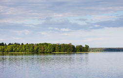 Serene landscape, a lake, forest and cloudy sky Stock Photos