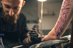 Serene male doing tattoo on arm Stock Photography