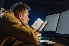 Serene male looking through book stock image