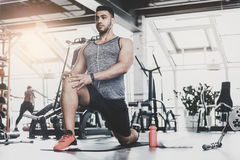 Serene male working out in keep-fit studio. Low angle full length serious bearded athlete engaging in sports activities while hearing song in modern gym. Copy Royalty Free Stock Photography