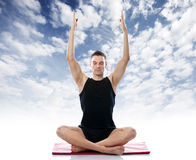 Serene man doing yoga  exercise against the sky Stock Image