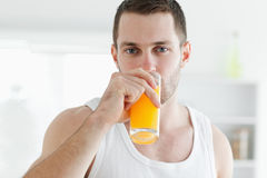 Serene man drinking orange juice. In his kitchen Stock Images