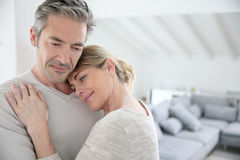 Serene mature couple embracing in living room Stock Photo