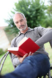 Serene mature man reading book in garden Stock Photo