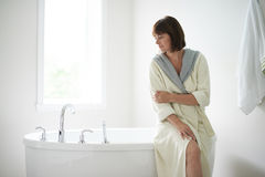 Serene mature woman sitting by a bathtub Royalty Free Stock Image