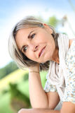 Serene mature woman sitting outdoor Stock Photos